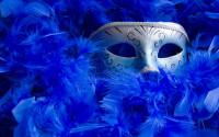 Venetian mask among bright blue feathers.